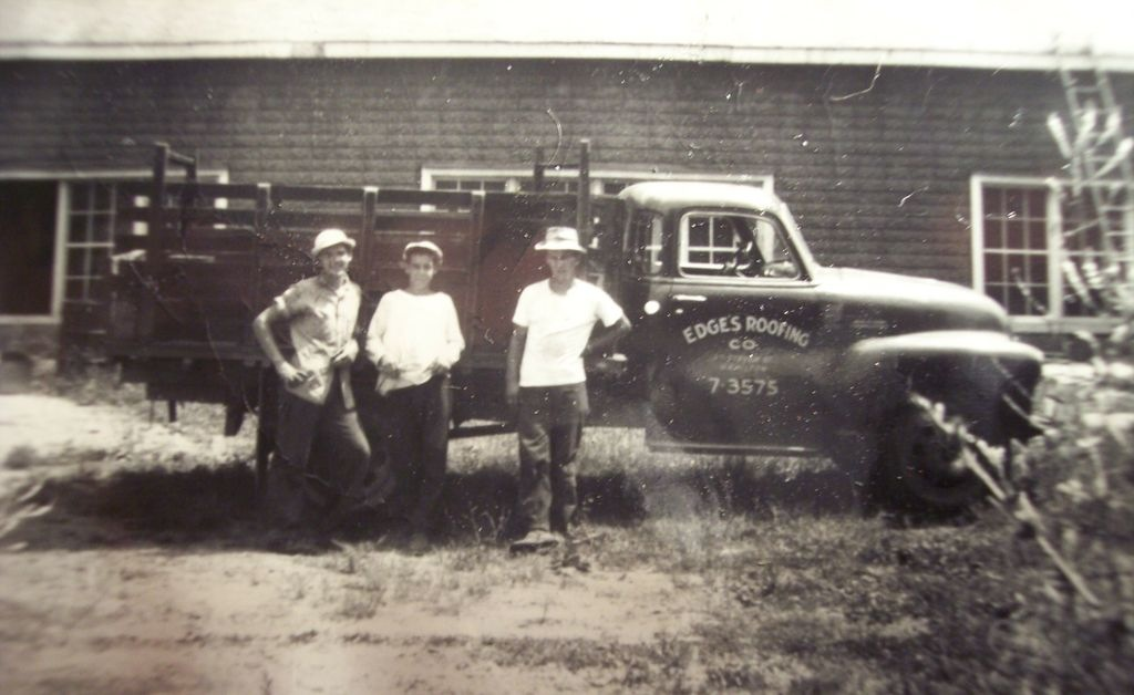 Older photo of the company's truck and workers